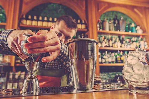 Barmann macht einen alkoholischen cocktail an der theke an der bar Kostenlose Fotos