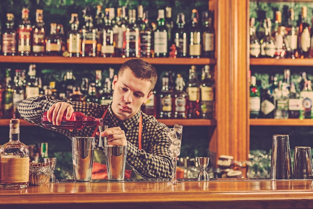 Barmann macht einen alkoholischen cocktail an der theke Kostenlose Fotos