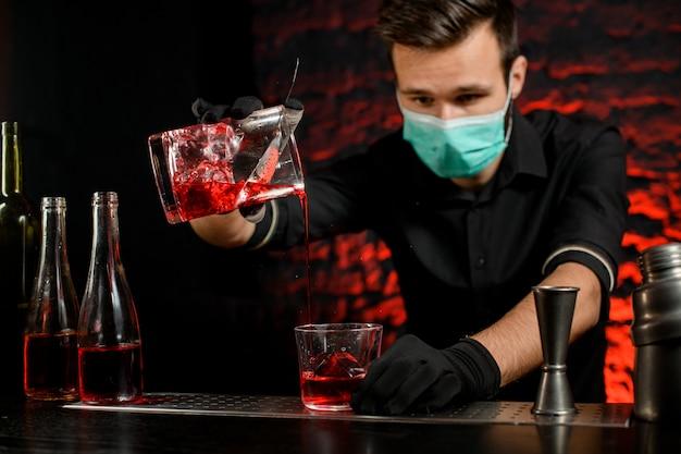 Barmann mit maske gießt meisterhaft kalten cocktail in glas Premium Fotos