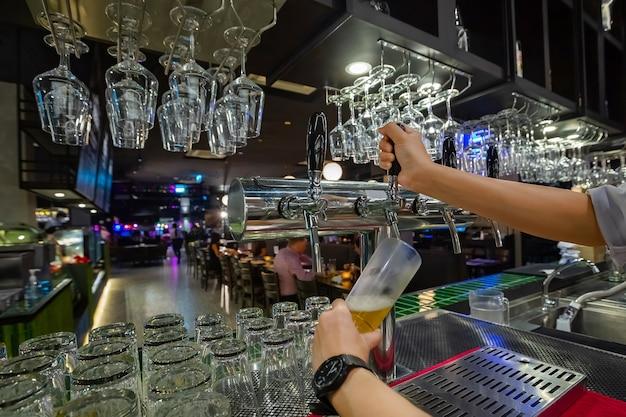 Barmannhände gießen ein lagerbier in ein glas Premium Fotos