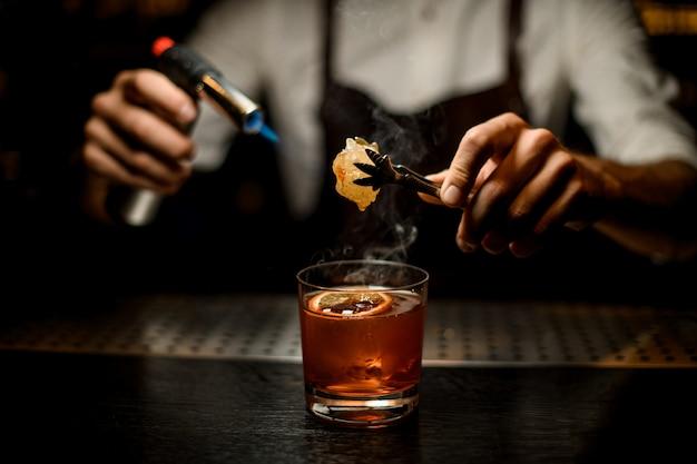 Barmixer, der ein braunes cocktailschmelzkaramel mit einem brenner über der zitronenscheibe dient Premium Fotos