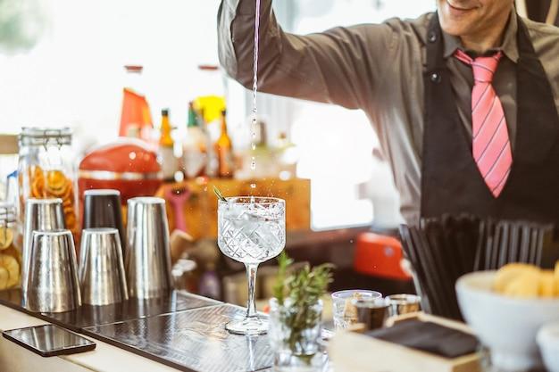 Barmixer, der ein cocktail in einem kristallglas in einer amerikanischen bar mischt Premium Fotos