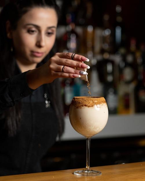 Barmixerfrau, die zimtpulver in milchiges cocktail hinzufügt. Kostenlose Fotos