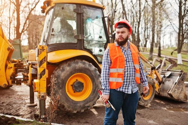Bartarbeitskraftmann-klagenbauarbeiter im orange sturzhelm der sicherheit, gegen traktor mit dem justierbaren schlüssel zur hand. Premium Fotos