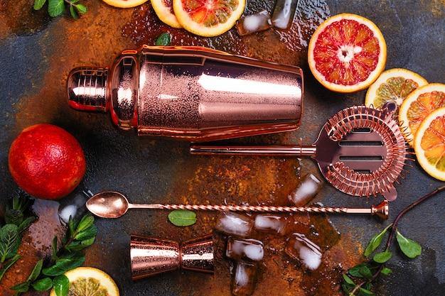 Barzubehör, getränkewerkzeuge und cocktailbestandteile auf rostiger steintabelle. Premium Fotos
