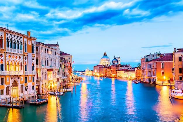 Basilika santa maria della salute und grand canal bei blauem stundensonnenuntergang in venedig, italien mit booten und reflexionen. Premium Fotos
