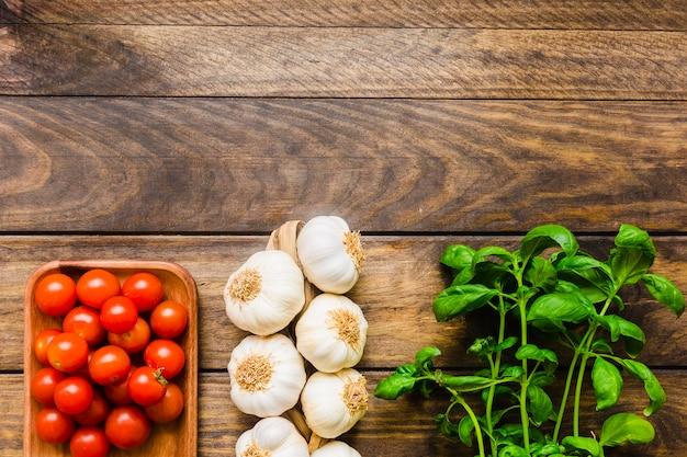 Basilikum in der nähe von knoblauch und tomaten Kostenlose Fotos