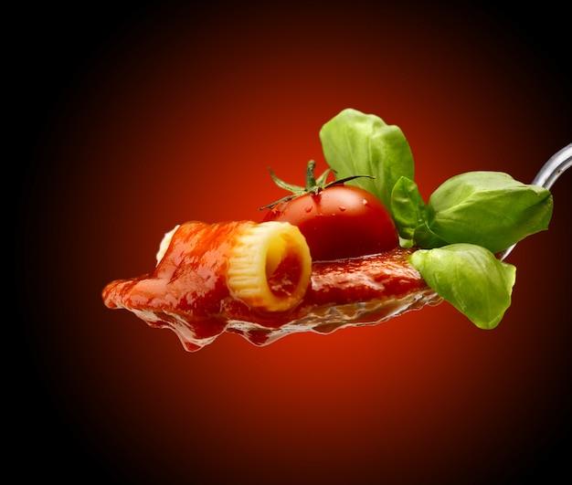 Basilikum in der nähe von nudeln und tomatensauce in einem löffel Premium Fotos