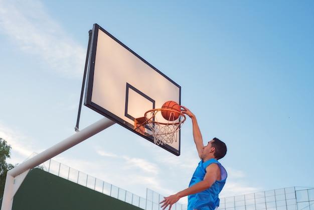 Basketballstraßenspieler, der einen slam dunk macht Premium Fotos