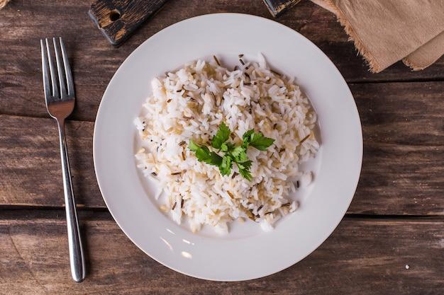 Basmatireis mit kräutern auf einer weißen platte auf einem holztisch Premium Fotos