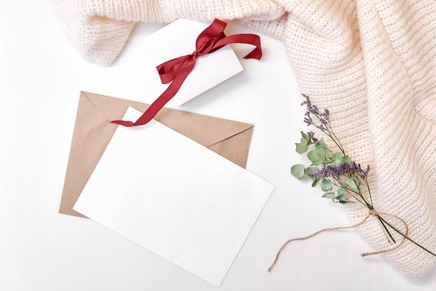 Basteln sie einen umschlag, papierrohling, geschenkbox mit schleife, gestrickter schal, getrocknete blumen und blätter Premium Fotos