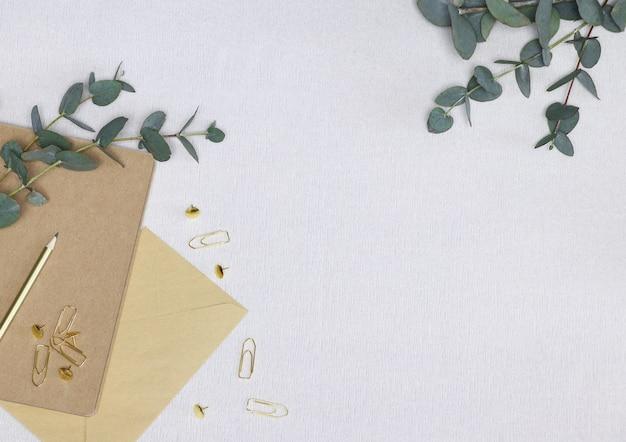Basteln sie notizen mit goldenen bleistift, büroklammern, umschlag und grünen eukalyptuszweigen Premium Fotos
