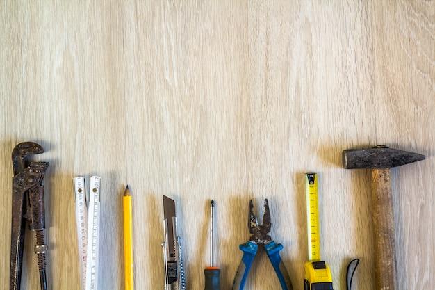 Bau-, gebäude- und reparaturwerkzeugsatz für hausarbeit über hölzernen hintergrund. ansicht von oben. Premium Fotos