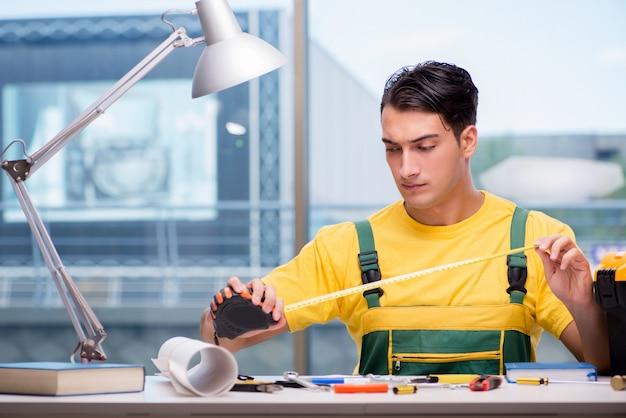 Bauarbeiter, der am schreibtisch sitzt Premium Fotos