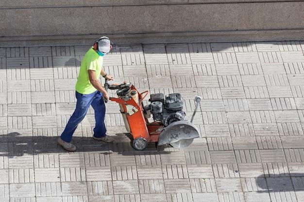 Bauarbeiter, der pflastersteinboden mit diamantsägeblattmaschine auf einem bürgersteig schneidet Premium Fotos
