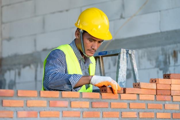 Bauarbeiter, der roten backstein mit kellenkittmesser für den neubau auf der baustelle installiert Premium Fotos