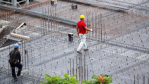 Bauarbeiter, die an einem wolkigen tag auf der baustelle arbeiten Kostenlose Fotos