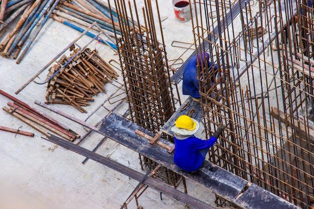 Bauarbeiter, die große stahlstab-verstärkungsstange an der baustellebaustelle herstellen. Premium Fotos
