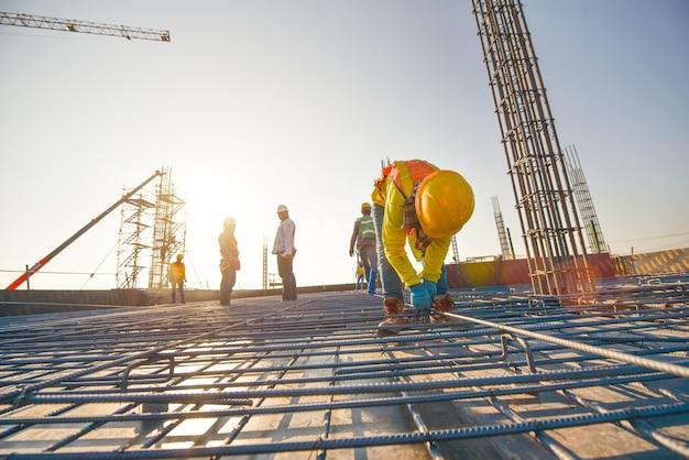 Bauarbeiter, die stahlverstärkungsstange an der baustelle herstellen Premium Fotos