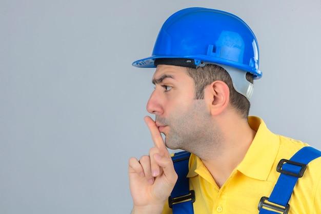 Bauarbeiter in uniform und blauem schutzhelm, der stille geste auf weiß lokalisiert macht Kostenlose Fotos