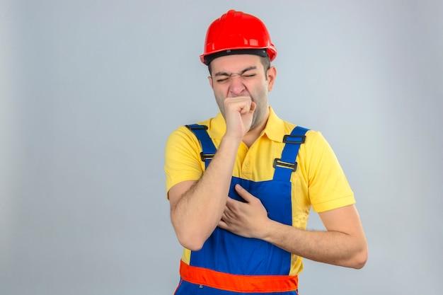 Bauarbeiter in uniform und rotem schutzhelm gelangweilt, gähnender müder kegelmund mit hand lokalisiert auf weiß Kostenlose Fotos