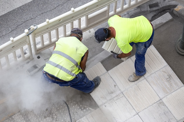 Bauarbeiter reparieren einen bürgersteig. wartungskonzept Premium Fotos