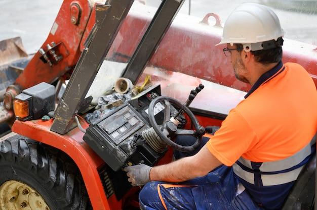 Bauarbeiter startet die baggermaschine. Premium Fotos