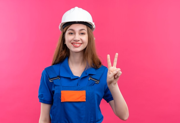 Bauarbeiterin der jungen frau in der bauuniform und im sicherheitshelm lächelnd, die fröhlich siegeszeichen auf nummer zwei über rosa wand stehend zeigen Kostenlose Fotos