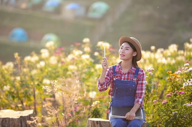 Bauernfrauen machen sich notizen im blumengarten. Kostenlose Fotos
