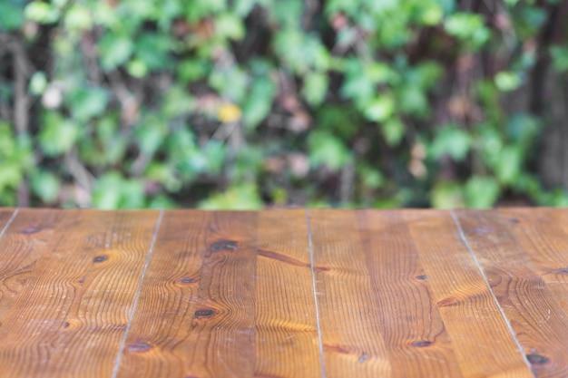 Bauholz Tischplatte auf Pflanzenwand Hintergrund Kostenlose Fotos