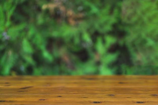 Bauholztischplatte auf unscharfem grünem Hintergrund Kostenlose Fotos