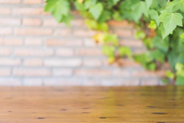 Bauholztischplatte nahe backsteinmauer und rebe Kostenlose Fotos