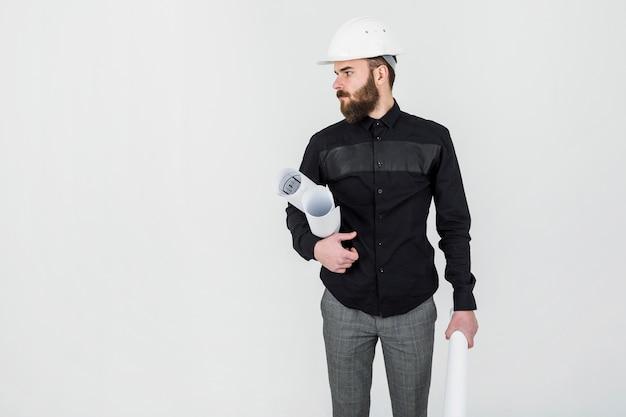 Bauingenieur, der plan in seiner hand gegen weißen hintergrund hält Premium Fotos