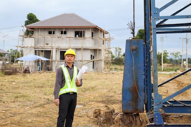 Bauingenieur des asiatischen geschäftsmannes im schutzhelm und im blaupausenpapier zur hand auf hausbaustelle Premium Fotos