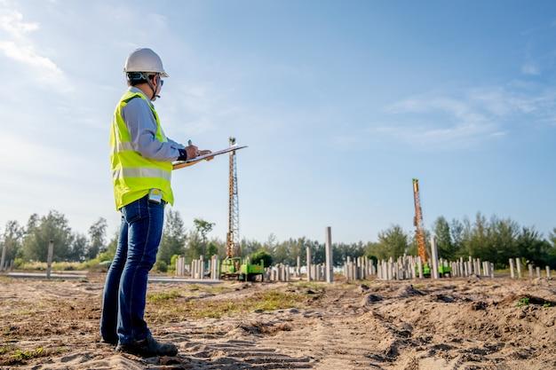 Bauingenieurinspektionsstapelarbeit an der infrastrukturbaustelle Premium Fotos