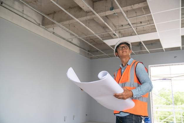 Baukonzept des ingenieurs und des architekten, die an der baustelle mit blauem druck arbeiten Premium Fotos