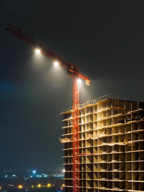 Baukran und unfertiges gebäude nachts. helle lichter montiert an einem kran. Premium Fotos