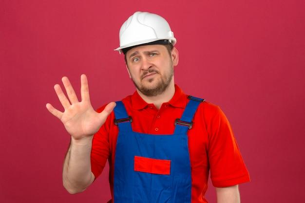 Baumeistermann, der bauuniform und sicherheitshelm trägt, zeigt und zeigt mit den fingern nummer fünf mit skeptischem ausdruck auf gesicht über isolierter rosa wand Kostenlose Fotos
