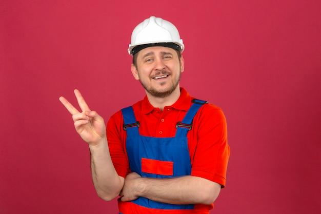Baumeistermann, der bauuniform und sicherheitshelm trägt, zeigt und zeigt mit den fingern nummer zwei oder siegeszeichen, das fröhlich über isolierte rosa wand lächelt Kostenlose Fotos