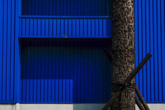 Baumstamm vor blauer strukturierter wand Kostenlose Fotos
