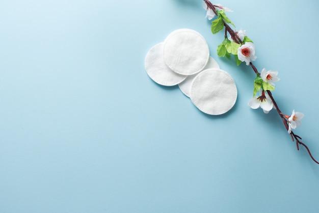 Baumwollauflagen für abbau make-up mit weißen blumen auf dem blauen hintergrund flatlay Premium Fotos