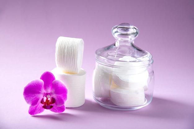 Baumwollschwämme in einem glasgefäß auf einem rosa hintergrund mit einer orchideenblume Premium Fotos