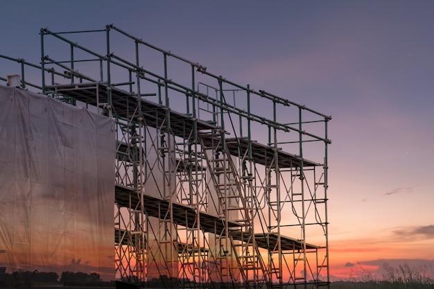 Baustelle mit gestellkontrollturm und gebäude mit sonnenunterganghintergrund Premium Fotos