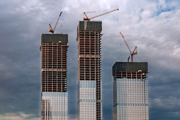 Baustelle, wolkenkratzer und kräne bei bewölktem himmel Premium Fotos