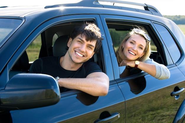 Bautiful glückliches junges paar, das das auto fährt Kostenlose Fotos