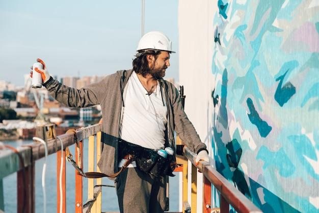 Bauunternehmer, künstler in großer höhe in einer gebäudewiege führt fassadenmalerei durch Premium Fotos