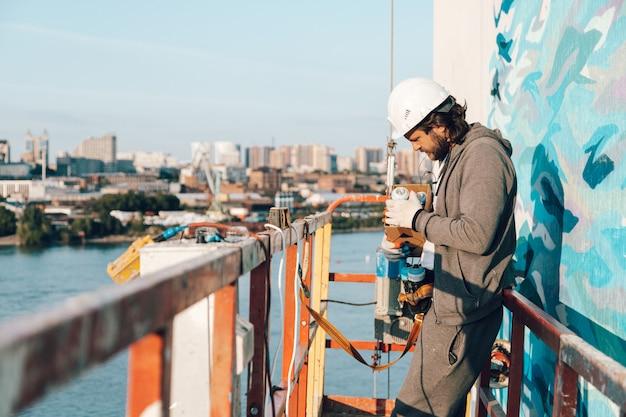Bauunternehmer, künstler in großer höhe in einer gebäudewiege holt eine sprühdose aus der schachtel, dekoriert und renoviert das haus Premium Fotos