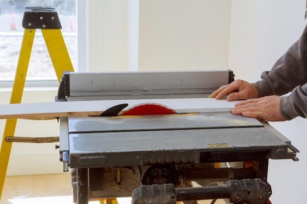 Bauunternehmerarbeitskraft, die kreissäge verwendet, um bretter auf einem neuen wohnungsbauprojekt zu schneiden Premium Fotos