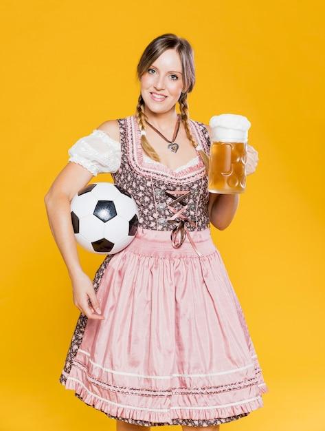Bayerisches mädchen, das ball und bierkrug hält Kostenlose Fotos