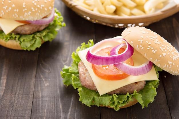 Bbq-hamburger mit pommes-frites auf dem holztisch. Premium Fotos